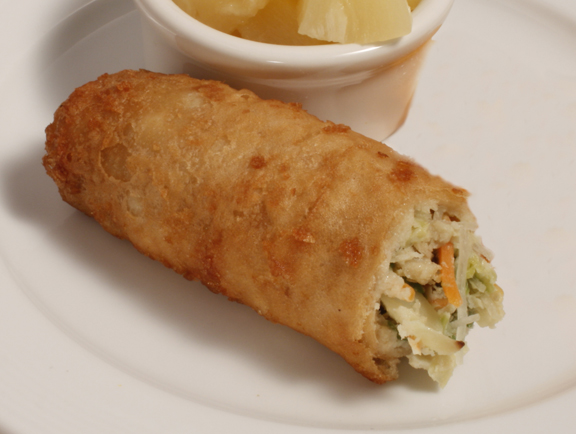 Plate of foodservice Golden Tiger Asian Chicken Egg Roll with Pineapple Chunks in a school setting