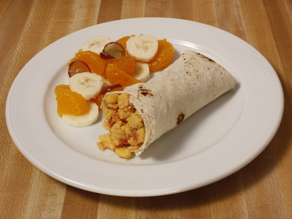 Plate of foodservice Butcher Boy Mexican Egg Cheese Breakfast Burrito with Fruit in a school setting