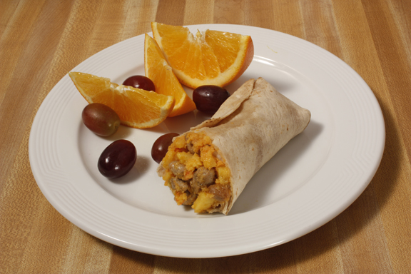 Plate of foodservice Egg, Sausage and Cheese Breakfast Burrito with Fruit in a school setting