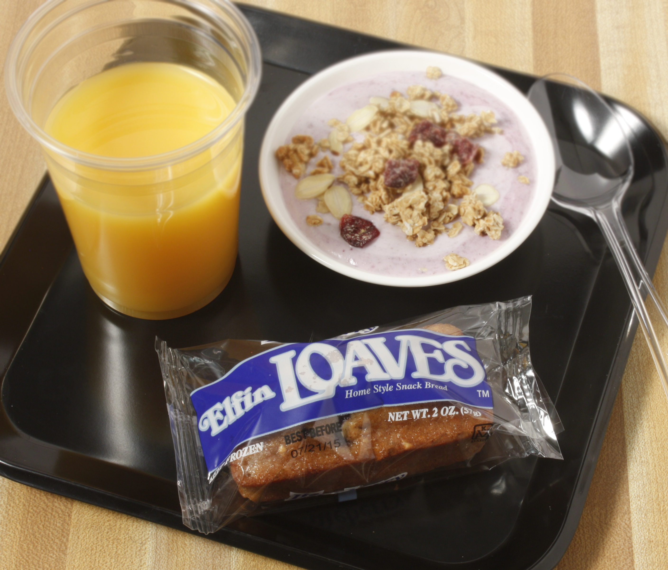 Plate of foodservice Whole Grain Blueberry Elfin Loaf with yogurt and Orange Juice in a school setting