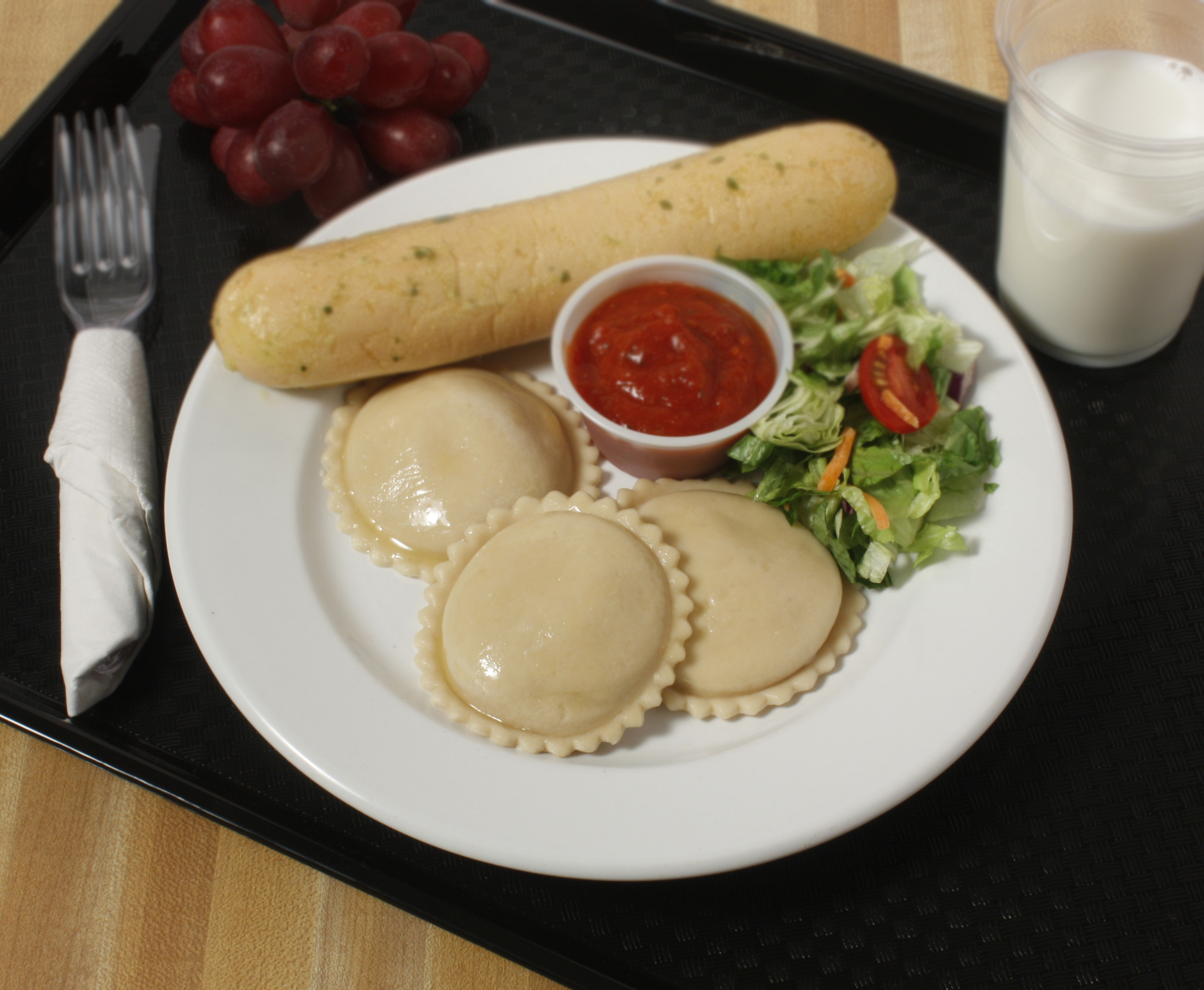 Plate of foodservice Bernardi Italian Ravioli with Salad and a Breadstick in a school setting